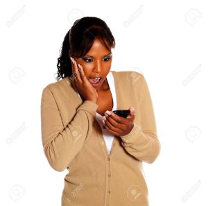 15426816-Surprised-black-woman-reading-a-message-on-cellphone-on-isolated-background-Stock-Photo