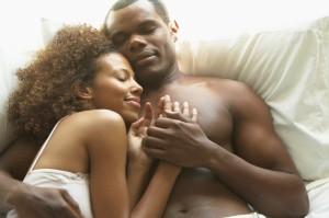 Couple Cuddling in Bed --- Image by © Dann Tardif/LWA/Corbis