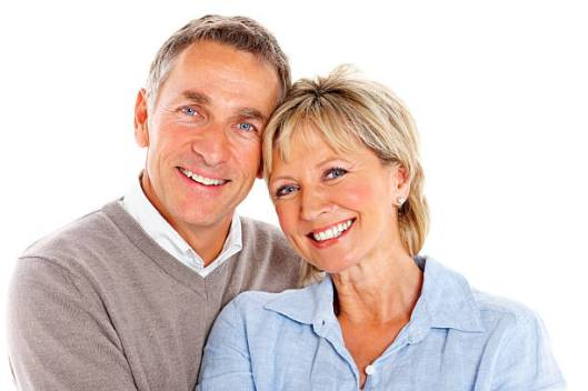 Portrait of loving mature couple smiling together against white background